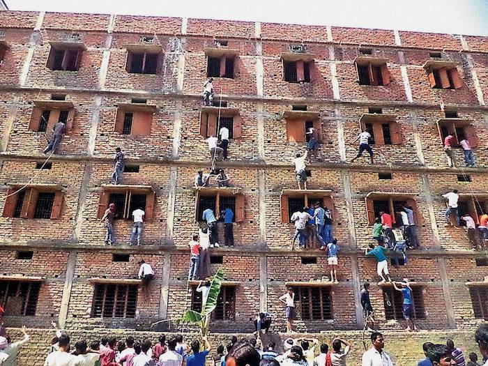 Youths climbing the building of an examination centre to help the candidates in cheating, by passing notes through the windows, during a Matriculation examination in Hajipur, Bihar in 2015