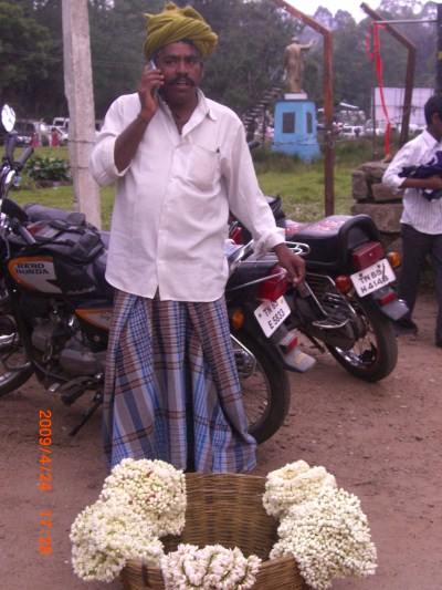 Flower man in Kodaikanal using a mobile