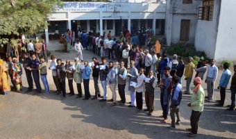 People wait with their identity cards to cast their votes for the Assembly elections, in Jabalpur, Madhya Pradesh, Wednesday, Nov 28, 2018.
