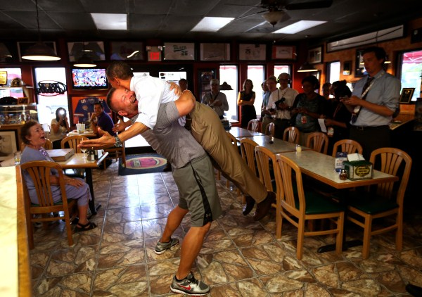 President Obama is lifted in the air by Scott Van Duzer, owner of the Big Apple Pizza owner